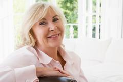 Woman in living room smiling - stock photo