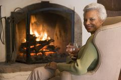 Woman in living room with drink smiling - stock photo