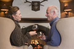 Couple sitting in living room by fireplace with drinks smiling - stock photo