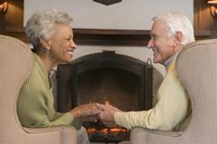 Couple sitting in living room by fireplace holding hands and smiling - stock photo