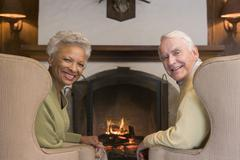 Couple sitting in living room by fireplace smiling Stock Photos
