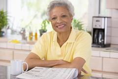 Woman with a newspaper smiling - stock photo