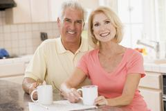 Couple in kitchen with coffee smiling Stock Photos