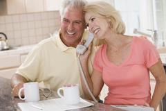 Couple in kitchen with coffee using telephone together and smiling - stock photo