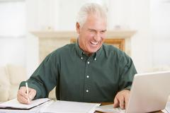 Man in dining room with laptop and paperwork smiling - stock photo