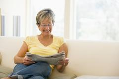 Woman relaxing with newspaper in living room smiling - stock photo
