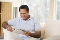 Man relaxing with newspaper in living room and smiling - stock photo