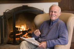 Man sitting in living room by fireplace with newspaper smiling - stock photo