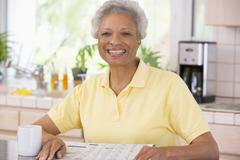 Woman relaxing with newspaper in kitchen and smiling Stock Photos