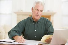 Man in dining room with laptop and paperwork looking unhappy - stock photo