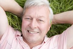 Man lying in grass smiling - stock photo