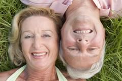 Couple relaxing outdoors and smiling - stock photo