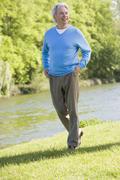 Man walking outdoors at park by lake smiling Stock Photos