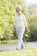 Woman walking outdoors at park by lake smiling - stock photo
