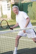 Man playing tennis and smiling Stock Photos
