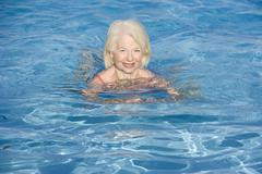 Woman swimming in outdoor pool smiling Stock Photos