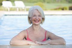 Woman in outdoor pool smiling - stock photo