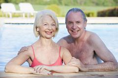 Couple in outdoor pool smiling - stock photo