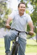 Man on bike outdoors smiling - stock photo