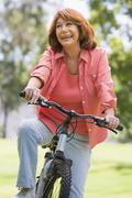 Woman on bike outdoors smiling Stock Photos