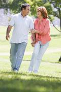 Couple holding hands outdoors by lake smiling - stock photo