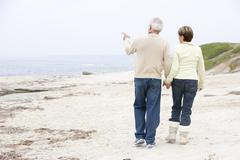 Couple at the beach holding hands and pointing Stock Photos