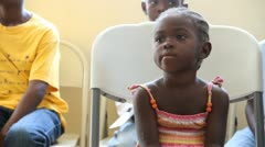 Child waits for Dr. at vaccination clinic Stock Footage