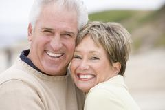 Couple at the beach smiling Stock Photos