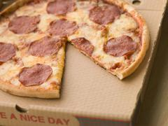 Pepperoni Pizza in a Take Away Box with a Slice Taken - stock photo