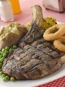Ribeye Steak on the bone with Baked Potato Peas Onion Rings and Corn Stock Photos