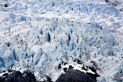 blue icy portage glacier with rock and crevaces alaska - stock photo