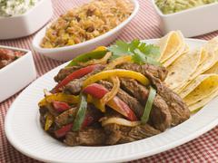 Steak Fajitas with Jambalaya Guacamole Salsa and Sour Cream Stock Photos
