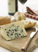 Wedge of Roquefort Cheese with Rustic Baguette and Red Wine - stock photo