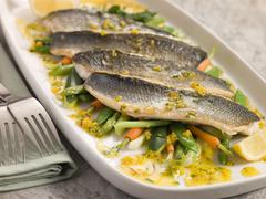 Fillets of Sea bass with Baby Vegetables and Saffron Butter Stock Photos