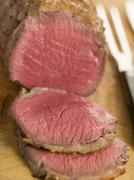 Roast Topside of British Beef carved on a Chopping Board Stock Photos