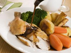 Gravy being Poured over a plate of Roast Chicken Stock Photos