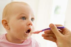 Mother feeding baby food to baby Stock Photos