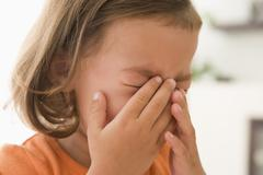 Stock Photo of Young girl indoors crying