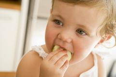Young girl eating apple indoors Stock Photos