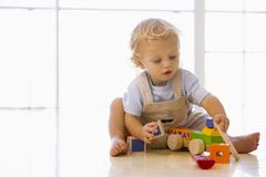 Baby indoors playing with toy truck - stock photo