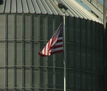 American flag waves in front of grain elevator Stock Footage