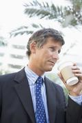 Businessman outdoors drinking coffee Stock Photos