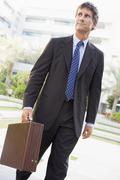 Businessman walking outdoors - stock photo