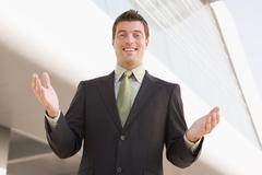 Businessman standing outdoors by building with hands out Stock Photos