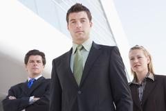 Three businesspeople standing outdoors by building - stock photo