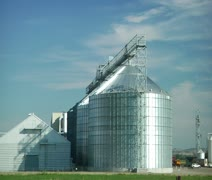 Wide panning shot of silver grain elevators and blue sky Stock Footage