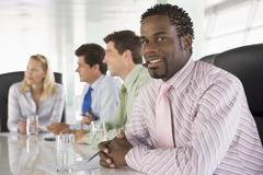 Four businesspeople in a boardroom smiling - stock photo