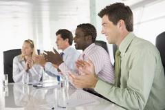 Four businesspeople in a boardroom applauding Stock Photos