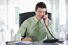 Businessman sitting in office with personal organizer on telephone Stock Photos