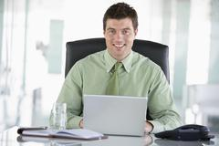 Stock Photo of Businessman sitting in office with personal organizer using laptop smiling